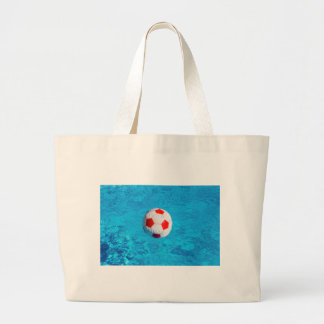 Beach ball floating  in blue swimming pool large tote bag