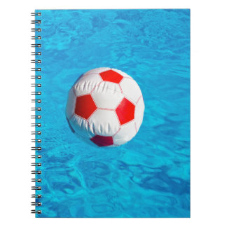 Beach ball floating  in blue swimming pool notebook