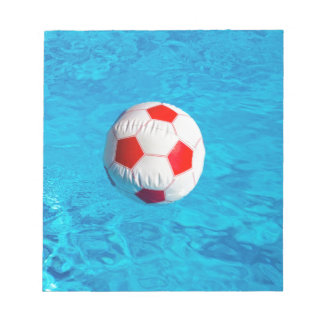 Beach ball floating  in blue swimming pool notepad