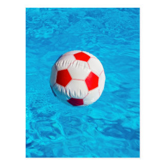 Beach ball floating  in blue swimming pool postcard