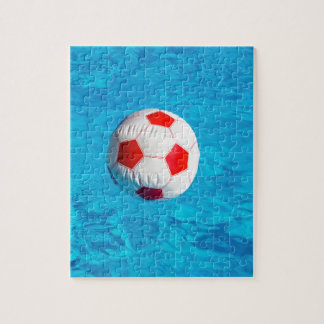 Beach ball floating  in blue swimming pool puzzle