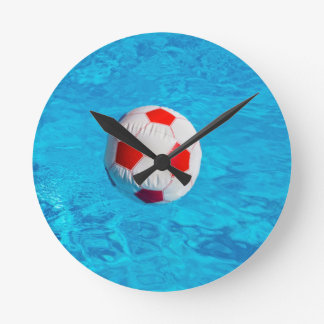 Beach ball floating  in blue swimming pool round clock