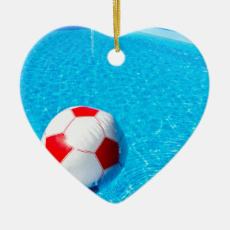 Beach ball floating on water in swimming pool ceramic heart ornament