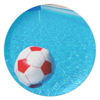 Beach ball floating on water in swimming pool dinner plates