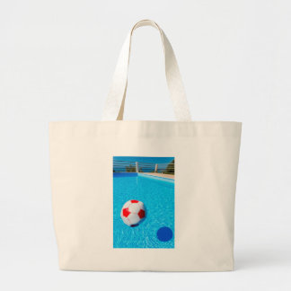 Beach ball floating on water in swimming pool large tote bag