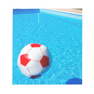 Beach ball floating on water in swimming pool notepad