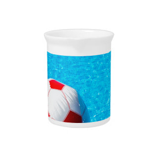 Beach ball floating on water in swimming pool pitcher