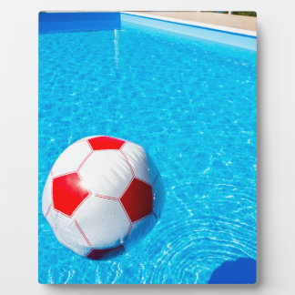 Beach ball floating on water in swimming pool plaque
