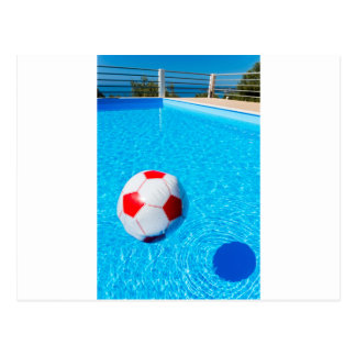 Beach ball floating on water in swimming pool postcard