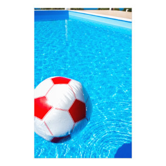 Beach ball floating on water in swimming pool stationery
