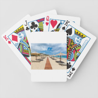 Beach umbrellas and loungers at greek sea bicycle playing cards
