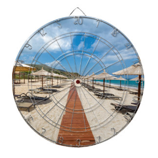 Beach umbrellas and loungers at greek sea dartboard