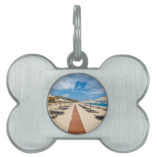 Beach umbrellas and loungers at greek sea pet name tag