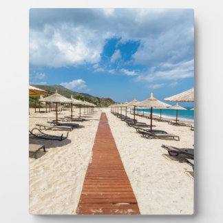 Beach umbrellas and loungers at greek sea plaque
