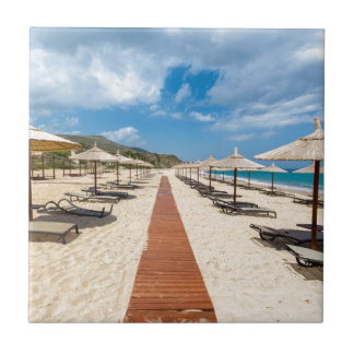 Beach umbrellas and loungers at greek sea tile