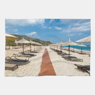 Beach umbrellas and loungers at greek sea towel