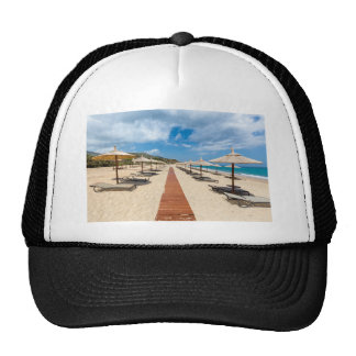 Beach umbrellas and loungers at greek sea trucker hat