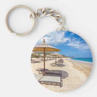 Beach umbrellas in rows on sandy beach with sea basic round button keychain