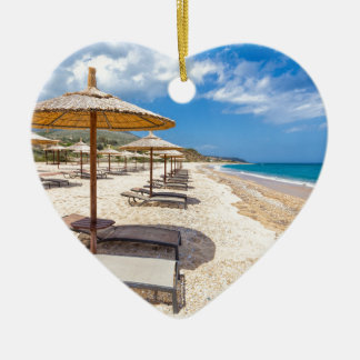 Beach umbrellas in rows on sandy beach with sea ceramic heart ornament