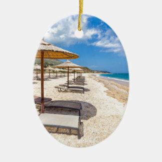 Beach umbrellas in rows on sandy beach with sea ceramic oval ornament