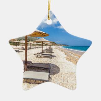 Beach umbrellas in rows on sandy beach with sea ceramic star ornament