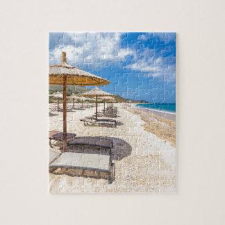 Beach umbrellas in rows on sandy beach with sea jigsaw puzzle