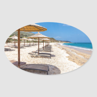 Beach umbrellas in rows on sandy beach with sea oval sticker