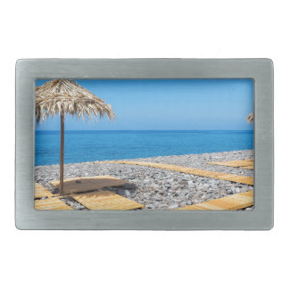 Beach umbrellas with path and stones at coast belt buckle