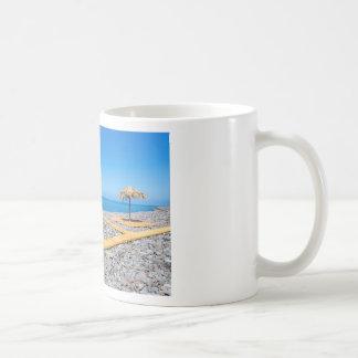 Beach umbrellas with path and stones at coast coffee mug