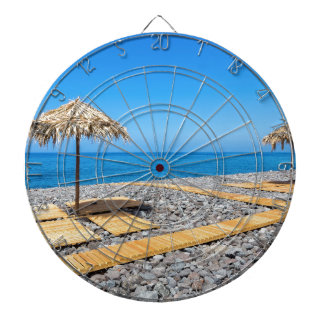 Beach umbrellas with path and stones at coast dartboard