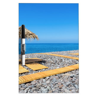 Beach umbrellas with path and stones at coast dry erase board