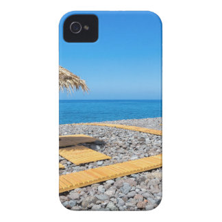 Beach umbrellas with path and stones at coast iPhone 4 cover