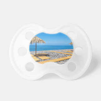 Beach umbrellas with path and stones at coast pacifiers