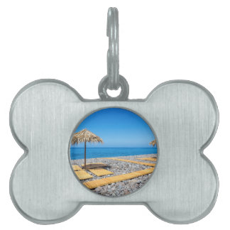 Beach umbrellas with path and stones at coast pet ID tags