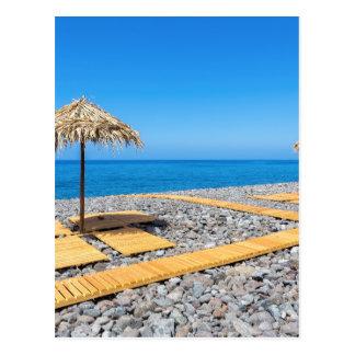 Beach umbrellas with path and stones at coast postcard