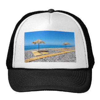 Beach umbrellas with path and stones at coast trucker hat