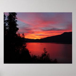 Beau lever de soleil rouge au-dessus d'un lac poster
