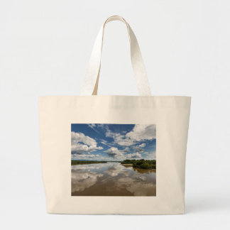 Beautiful clouds over river, reflection in water large tote bag