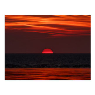 Beautiful image of the sun setting over the water postcard