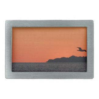 Beautiful sea sunset with island silhouette belt buckle