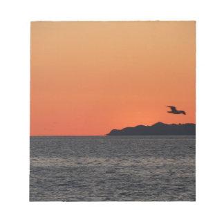 Beautiful sea sunset with island silhouette notepad