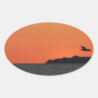 Beautiful sea sunset with island silhouette oval sticker