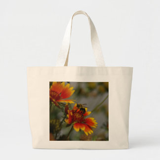 Bee foraging on a flower large tote bag