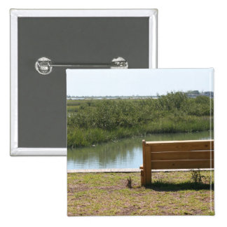 Bench by river with grass and water buttons