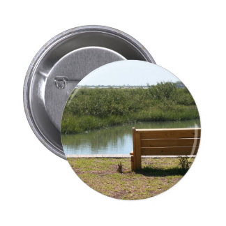 Bench by river with grass and water pinback button