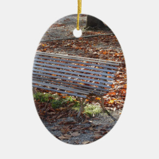 Bench in autumn park with dead leaves ceramic oval ornament