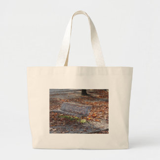 Bench in autumn park with dead leaves large tote bag