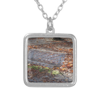 Bench in autumn park with dead leaves silver plated necklace