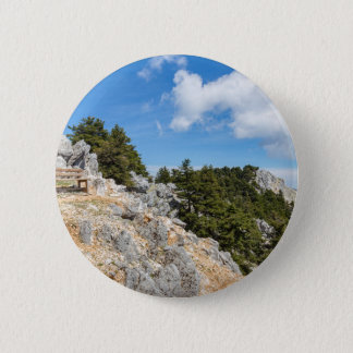 Bench on rocky mountain with trees and blue sky 2 inch round button
