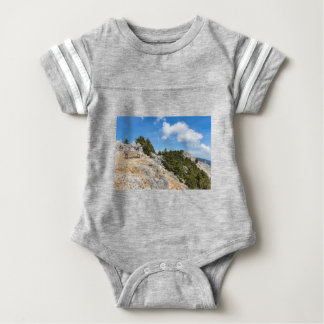Bench on rocky mountain with trees and blue sky baby bodysuit